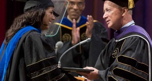 Purdue President Mitchell E. Daniels Jr., presents a diploma to a new graduate during commencement ceremonies on Saturday (Aug. 3) in the Elliott Hall of Music. (Purdue Photo/Mark Simons)